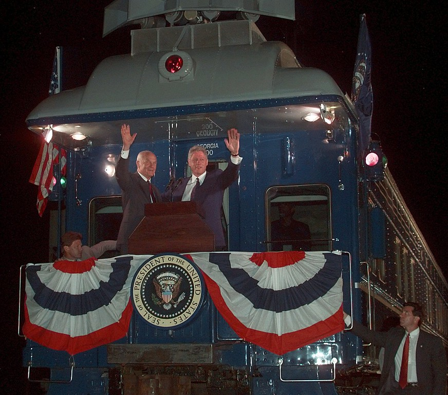 . President Clinton waves with Sen. John Glenn (D-OH), from the rear of the Century 21st Express train before departing  Chillicothe, Ohio, Sunday, Aug. 25, 1996 as part of five-state train tour en route to Chicago. (AP Photo/Greg Gibson)