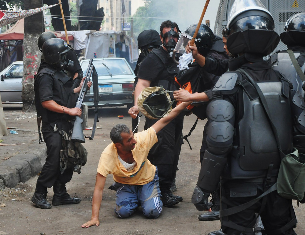 . Egyptian security forces detain a supporter of ousted Islamist President Mohammed Morsi as they clear a sit-in camp set up near Cairo University in Cairo\'s Giza district, Egypt, Wednesday, Aug. 14, 2013.  (AP Photo/Hussein Tallal)