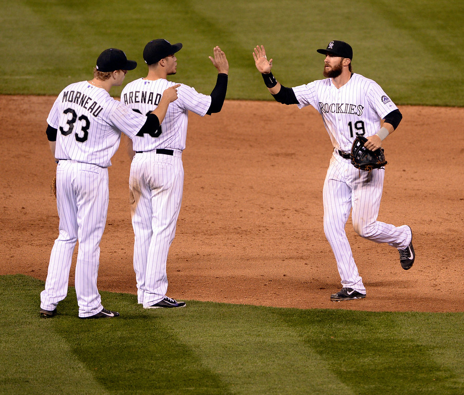 . DENVER, CO - APRIL 18: Colorado\'s Justin Morneau, Nolan Arenado, and Charlie Blackmon celebrated the win Friday night. The Colorado Rockies defeated the Philadelphia Phillies 12-1 Friday night, April 18, 2014 at Coors Field.  (Photo by Karl Gehring/The Denver Post)