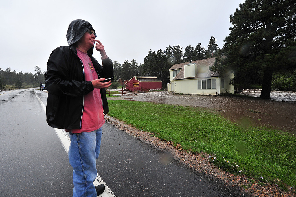 . Cindy Knight can only watch as the Fish Creek rises around her house on Thursday, Sept. 12, 2013. While the flood waters were taking her back deck off, her concern was for her cat trapped inside. Walt Hester/Estes Park Trail-Gazette