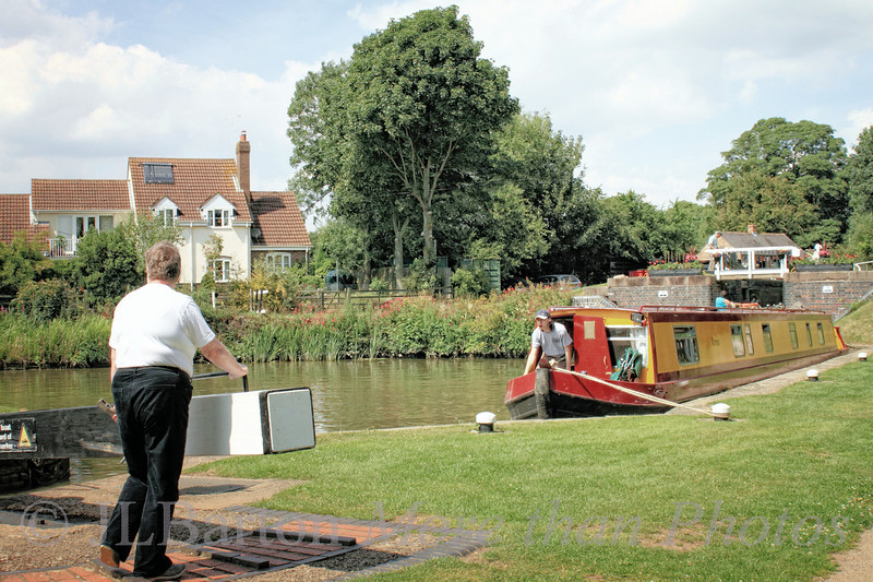 Working the Locks 2011-07-18  One more from the hotel, then we are on the road again.  Here is the first mate preparing the next lock, crew (responsible for windlass and rope work) just exiting the boat, and our boat waiting between locks on the Watford flight of the Grand Union Canal.  Many many thanks for the many comments on yesterday's shot.  I'm very grateful.