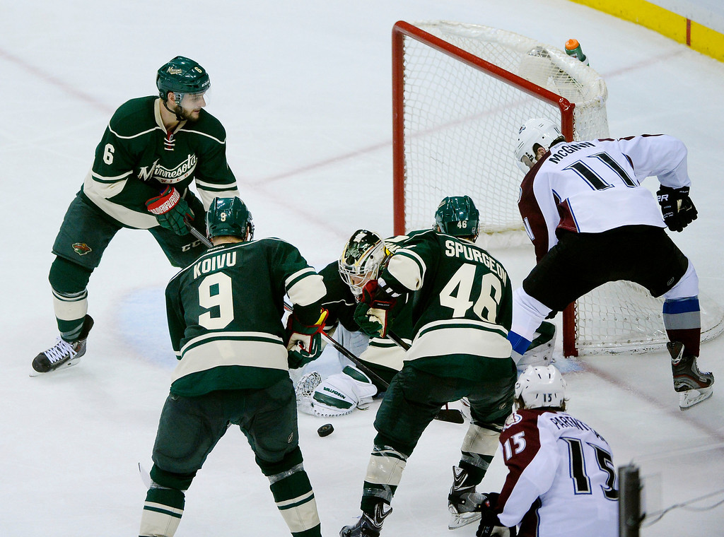 . Minnesota goalie Darcy Kuemper jumped on a loose puck in the third period with Colorado wing Jamie McGinn camped out on the pipe.   (Photo by Karl Gehring/The Denver Post)