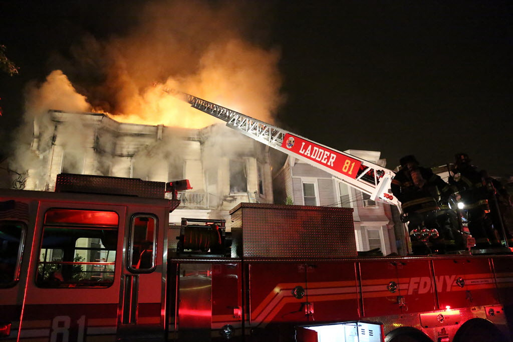 . Firefighters battle a fire that tore through three townhouses on New York City\'s Staten Island early Thursday, June 5, 2014.  (AP Photo/Staten Island Advance, Ryan Lavis)