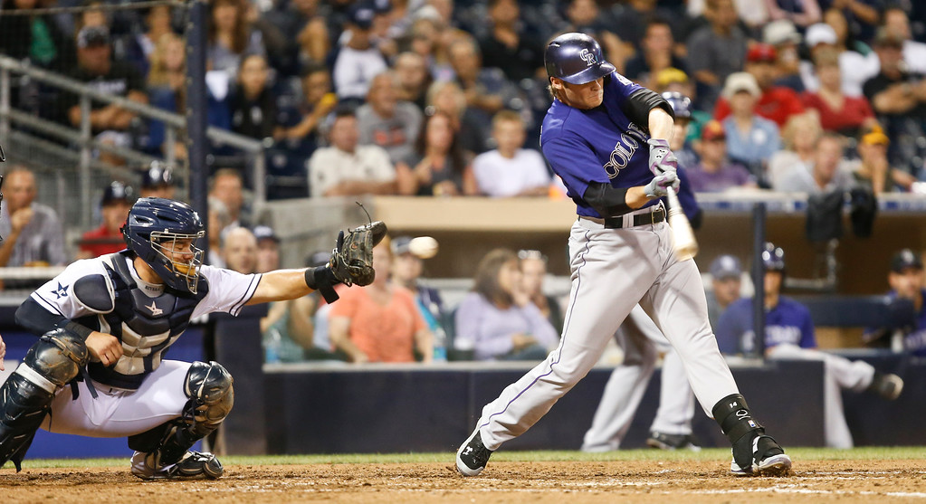 . Colorado Rockies\' Josh Rutledge  strikes out swinging with the bases loaded against the San Diego Padres during the fifth inning of a baseball game Monday, Sept. 22, 2014, in San Diego. The Padres\' catcher is Rene Rivera.  (AP Photo/Lenny Ignelzi)