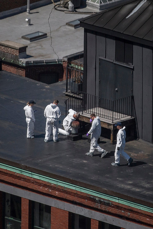 . Investigators search for evidence on the rooftop of a building located above the site of a bomb blast on Boylston Street two-days after multiple explosions at the Boston Marathon killed three and injured 176 in Boston, Massachusetts April 17, 2013. Investigators believe they have identified a suspect in the Boston marathon bombing from security video, a U.S. law enforcement source said.  REUTERS/Adrees Latif