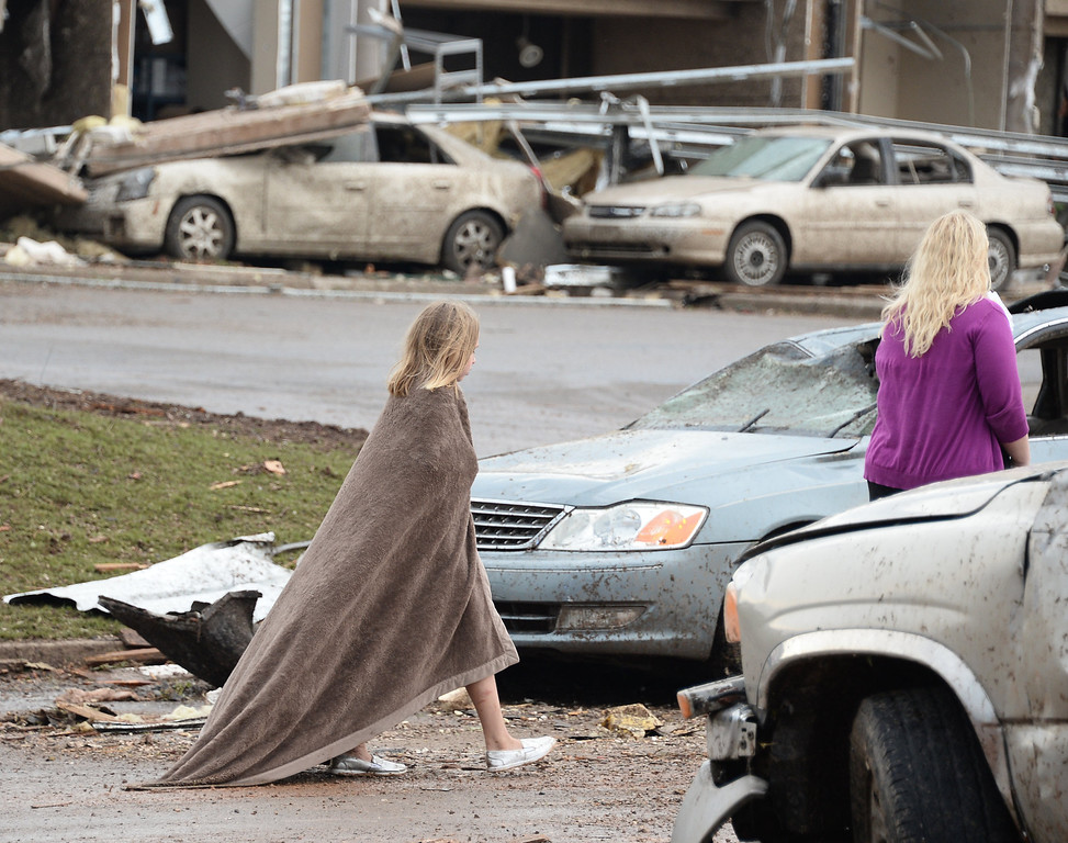 . A little girl tries to keep warm near the Moore Hospital. People look for victims at the Moore hospital. A tornado devastated the Oklahoma City suburb of Moore on Monday, ripping up at least two elementary schools and a hospital and leaving a wake of tangled wreckage and death. 