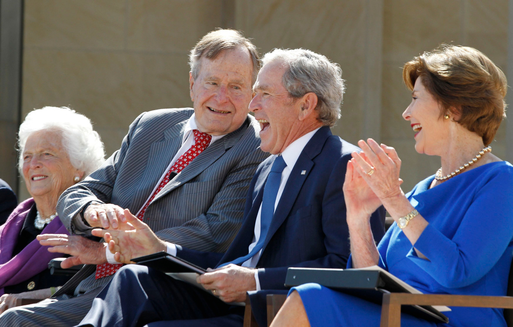 . Former U.S. presidents George W. Bush (C) and his father George H.W. Bush laugh alongside former first ladies Laura Bush (R) and Barbara Bush (L) during the dedication ceremony for the George W. Bush Presidential Center in Dallas, April 25, 2013.   Obama is in Texas to stand shoulder-to-shoulder with former president George W. Bush in what could serve as a powerful reminder of the ongoing struggle against terrorism, from the Sept. 11 attacks to the Boston Marathon bombings. REUTERS/Jason Reed