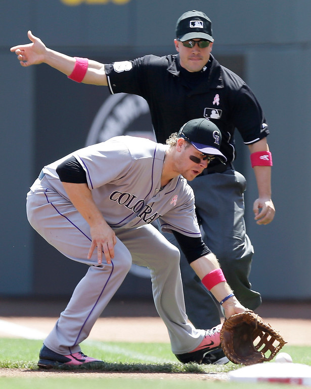 . Colorado Rockies first baseman Justin Morneau fields a ball hit by Cincinnati Reds\' Joey Votto that was ruled fair by umpire Chris Segal, rear, in the first inning of a baseball game, Sunday, May 11, 2014, in Cincinnati. Morneau touched first for the out. (AP Photo/Al Behrman)
