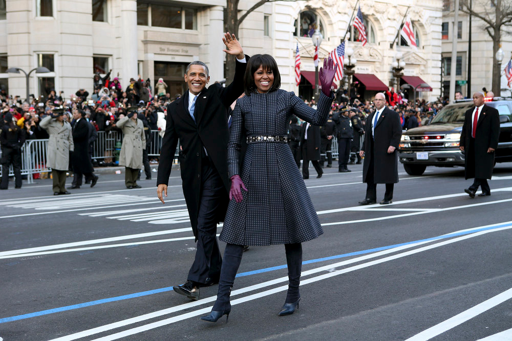 Description of . President Barack Obama and first lady Michelle Obama wave as they walk down Pennsylvania Avenue in Washington, Monday, Jan. 21, 2013, during the inaugural parade route , after his ceremonial swearing-in on Capitol Hill during the 57th Presidential Inauguration. (AP Photo/Doug Mills)