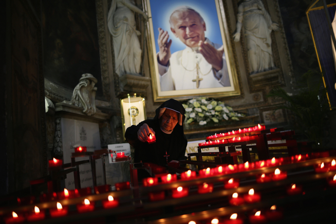 . A nun arranges candles underneath an image of the late Pope John Paul II at the Polish Church, Santo Spirito in Sassia, Sanctuary of Divine Mercy on April 26, 2014 in Vatican City, Vatican. Dignitaries, heads of state and Royals from Europe and across the World are gathering in the Vatican ahead of tomorrow\'s canonisations. The late Pope John Paul II and Pope John XXIII will be canonised on Sunday April 27, inside the Vatican when 800,000 pilgrims from around the world are expected to attend.   (Photo by Dan Kitwood/Getty Images)