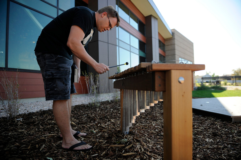 . Tobin Lopes plays chimes outside Anythink Library in Thornton while his four-year-old son explores other features in the new Nature Explore Classroom on Thursday, September 13, 2012. The area is Anythink Libraries\' first outdoor classroom and offers a space for climbing, building, performing and exploring outdoors next to the library. Lindsay Pierce, YourHub