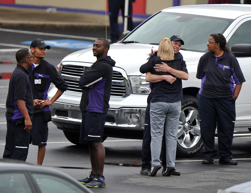 ". FedEx Employees and family members gather a skating rink following a shooting at the FedEx facility in Kennesaw, Ga., on Tuesday, April 29, 2014.  A shooter described as being armed with an assault rifle and having bullets strapped across his chest ""like Rambo\"" opened fire Tuesday morning at a FedEx station outside Atlanta, wounding at least six people before police found the suspect dead from an apparent self-inflicted gunshot.  (AP Photo/Atlanta Journal-Constitution, Brant Sanderlin)"