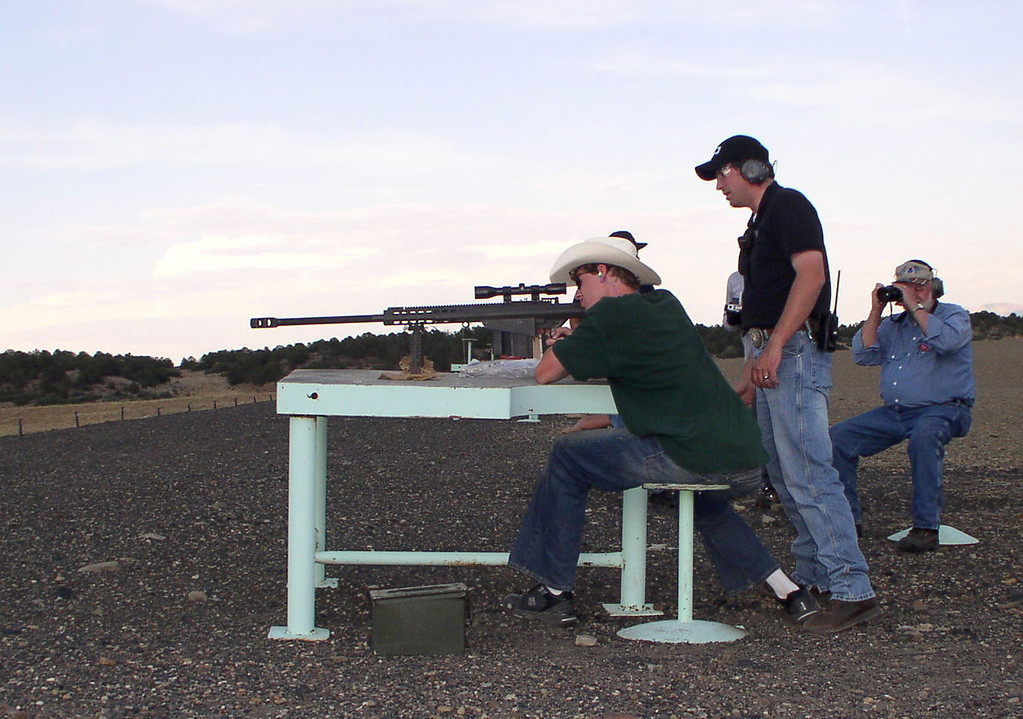 . In this photo provided by the National Rifle Association\'s Whittington Center, Wayne Armacost, standing, the center\'s executive director, helps teenager William Crouch of Texas take aim with a Barrett 50-caliber at a 1,000-yard shooting range at the center near Raton, N.M. in 2006. The center is billed as the most comprehensive shooting facility in the United States. Maintained by donor contributions and located in scenic northeastern New Mexico, the center is a monument to competitive, recreational and educational uses for firearms ranging from pistols to hunting rifles. (AP Photo/NRA Whittington Center)