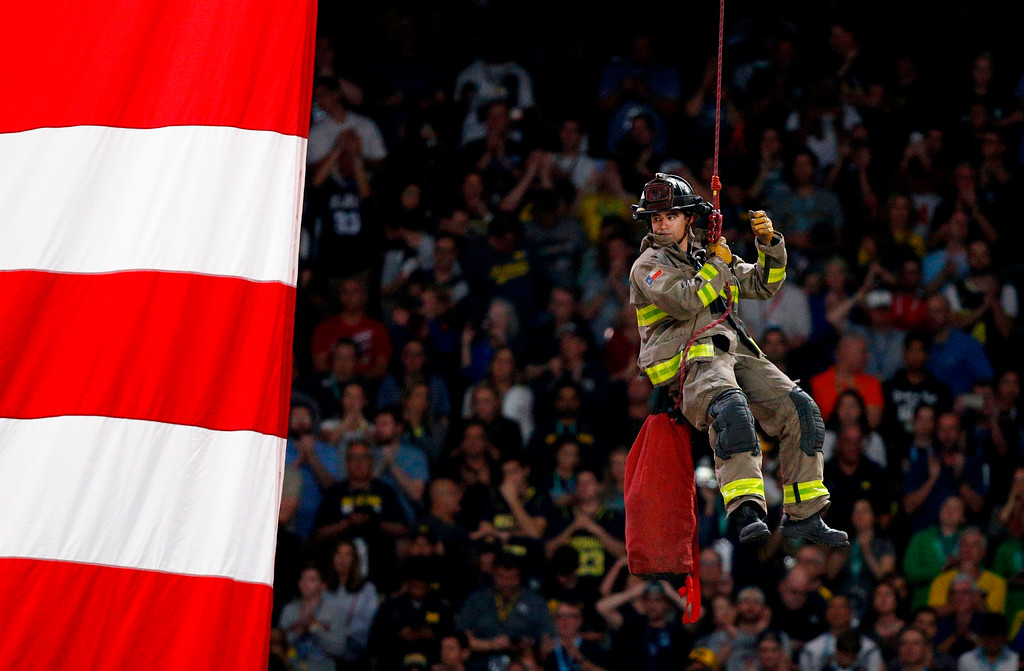 . A firefighter repels to the court during the national anthem before the championship game between Michigan and Villanova in the Final Four NCAA college basketball tournament, Monday, April 2, 2018, in San Antonio. (AP Photo/Brynn Anderson)