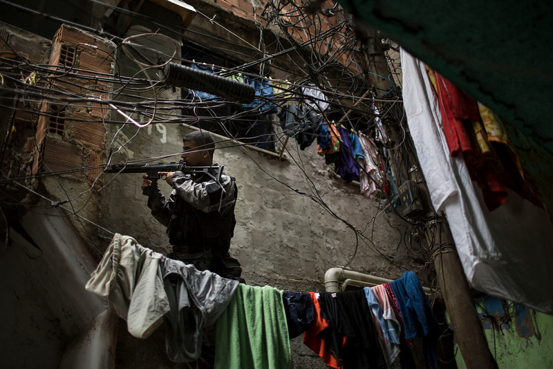 """. Framed behind a web of electrical wires and makeshift clotheslines, a military police officer takes position during an operation in the Mare slum complex, ahead of its \""""pacification,\"""" in Rio de Janeiro, Brazil, Tuesday, March 25, 2014. Elite federal police and army troops will be sent to the city to help quell a wave of violence in so-called \""""pacified\"""" slums. Recent attacks on police bases in the favelas is raising concerns about an ambitious security program that began in 2008, in part to secure the city ahead of this year\'s World Cup and the 2016 Olympics.. (AP Photo/Felipe Dana)"""