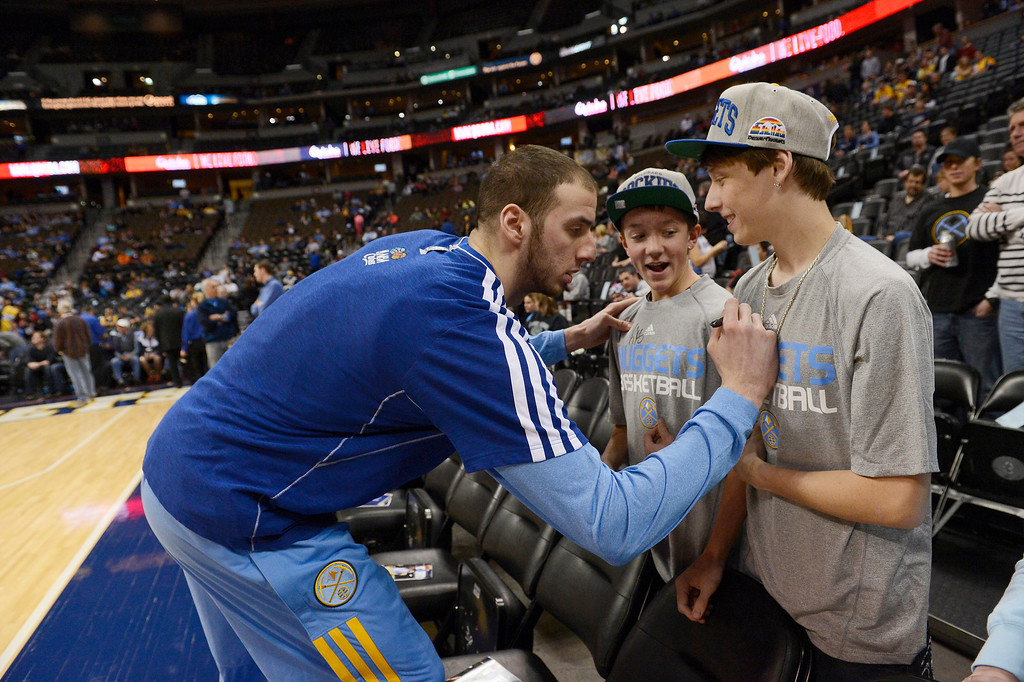 . Denver Nuggets center Kosta Koufos (41) signs an autograph for Kyle Gholson, 15, and  Michael Narvauz, 16, on January 28, 2013 at Pepsi Center before a game against the Indiana Pacers.  (Photo By John Leyba / The Denver Post)