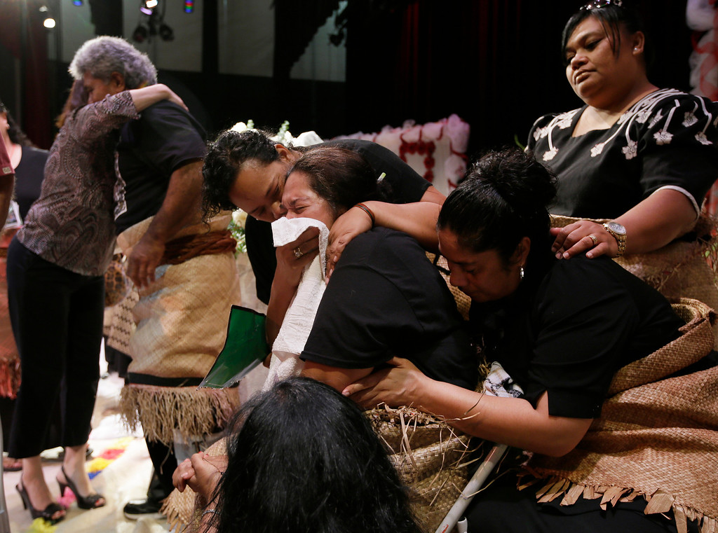 ". Tulima Uhatafe, center, with towel to her face, is consoled by relatives as she and husband Salesi Uhatafe, behind her, receive a line of guest by the caskets of their sons Polo Manukainiu, a Texas A&M redshirt freshman, and Andrew ""Lolo\"" Uhatafe, at a memorial service at Trinity High School, Friday, Aug. 9, 2013, in Euless, Texas. More than 2,500 people showed up to mourn the two who were killed in a single car accident in New Mexico, on July 29. Also killed in the accident was 18-year-old Utah recruit Gaius \""Keio\"" Vaenuku. (AP Photo/Tony Gutierrez)"