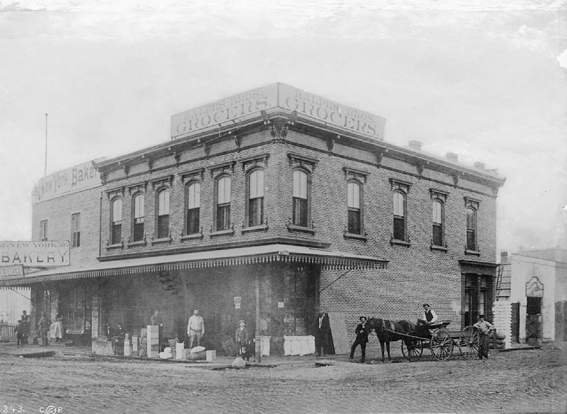 Exterior view of Ralphs Brothers Grocery and New York Bakery, located on the southwest corner of Sixth Street and Spring Street, 1886