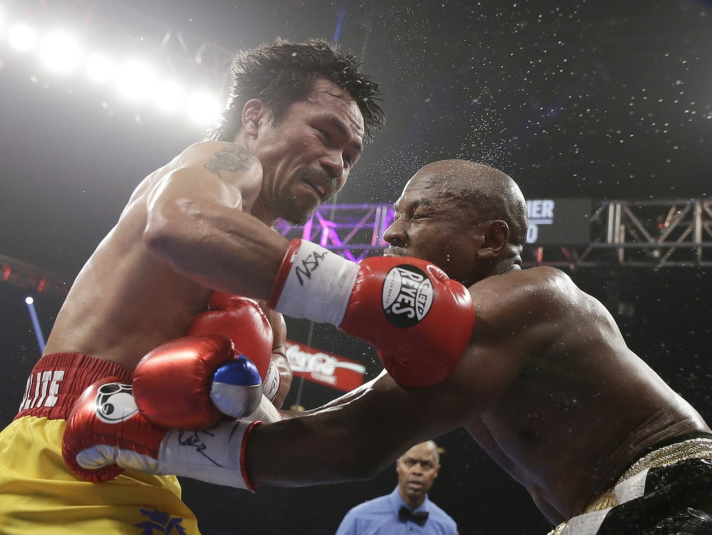 . Manny Pacquiao, from the Philippines, left, trades blows with Floyd Mayweather Jr., during their welterweight title fight on Saturday, May 2, 2015 in Las Vegas. (AP Photo/Isaac Brekken)