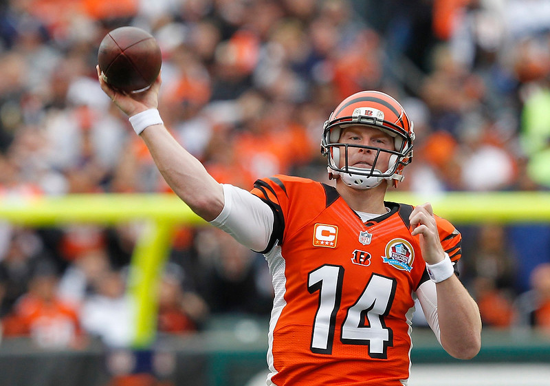 . Cincinnati Bengals quarterback Andy Dalton throws under pressure from the Dallas Cowboys\' defense during the first half of play in their NFL football game at Paul Brown Stadium in Cincinnati, Ohio, December 9, 2012.        REUTERS/John Sommers II