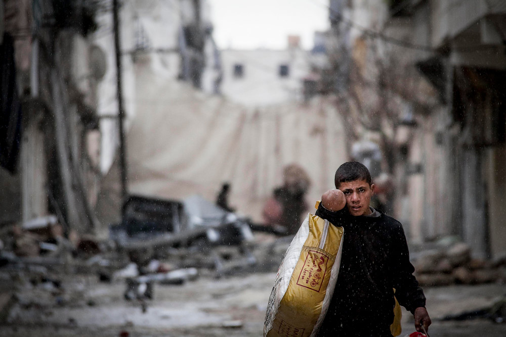 Description of . In this Tuesday, Dec. 11, 2012 photo, a Syrian boy carries his belongings after his home was damaged due to fighting between Free Syrian Army fighters and government forces in Aleppo, Syria. (AP Photo/Narciso Contreras)