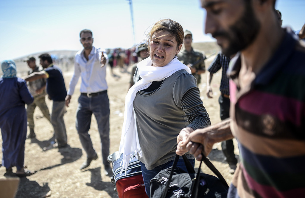 ". Syrian Kurds carry their belongings after they crosses the border between Syria and Turkey near the southeastern town of Suruc in Sanliurfa province, on September 20, 2014. Several thousand Syrian Kurds began crossing into Turkey on September 19 fleeing Islamic State fighters who advanced into their villages, prompting warnings of massacres from Kurdish leaders. Turkey on September 19 reopened its border with Syria to Kurds fleeing Islamic State (IS) militants, saying a ""worst-case scenario\"" could drive as many as 100,000 more refugees into the country. BULENT KILIC/AFP/Getty Images"
