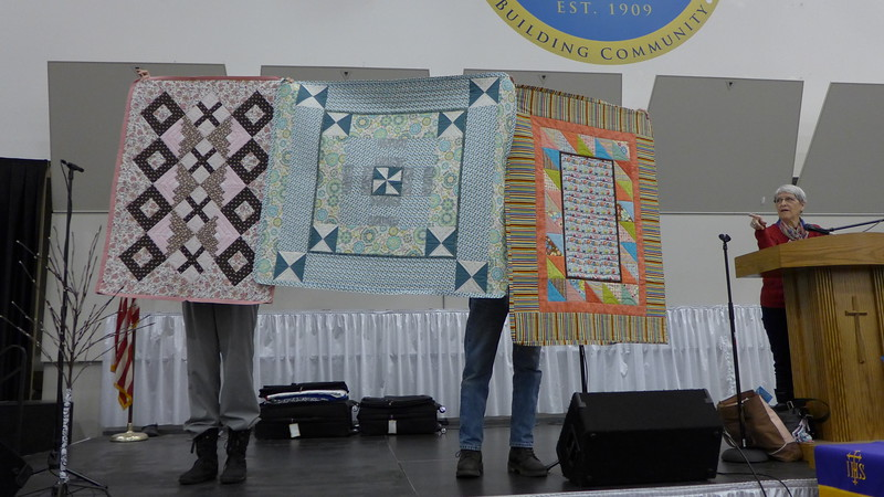 Jackie Borszich showing several quilts made for Heartwarmers
