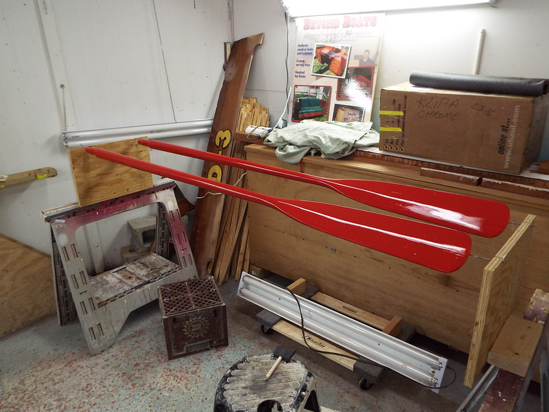 Oars with the first coat of red applied.