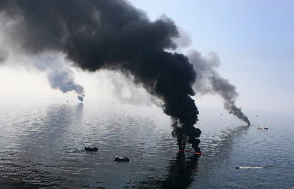. Smoke billows from a controlled burn of spilled oil off the Louisiana coast in the Gulf of Mexico coast line on June 13, 2010. A U.S. judge has accepted an agreement by BP Plc to plead guilty for its role in the Deepwater Horizon disaster and pay $4.5 billion in penalties for the worst offshore oil spill in U.S. History.  REUTERS/Sean Gardner