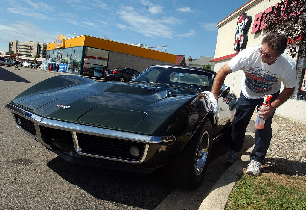 . Steve Broggi polishes his 1968 Corvette parked at the Mobil station at13 Mile Road  and Woodward Avenue in Royal Oak for the upcoming Woodward Dream Cruise. (Oakland Press Photo: Vaughn Gurganian)