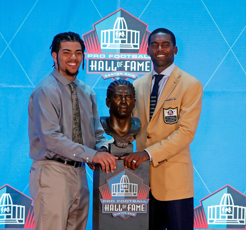 . Former NFL wide receiver Randy Moss, right, poses with a bust of himself and with his presenter, son Thaddeus Moss, during inductions at the Pro Football Hall of Fame, Saturday, Aug. 4, 2018 in Canton, Ohio. (AP Photo/Gene J. Puskar)