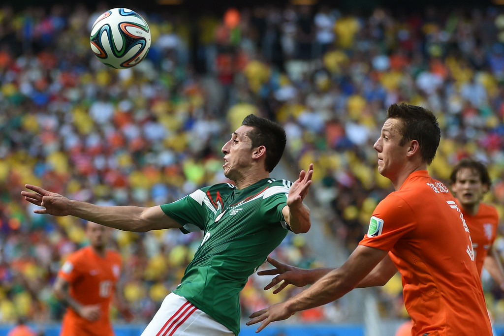 . Mexico\'s midfielder Hector Herrera (L) vies with Netherlands\' defender Stefan de Vrij during a Round of 16 football match between Netherlands and Mexico at Castelao Stadium in Fortaleza during the 2014 FIFA World Cup on June 29, 2014.   AFP PHOTO/ YURI CORTEZ