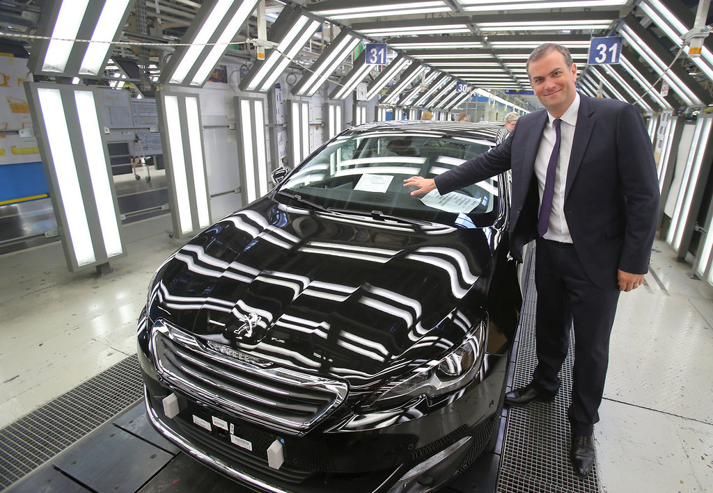 . The head of French carmaker Peugoet, Maxime Picat, pointing to the new 308 during an interview with the Associated Press on the quality control line at the Peugeot plant in Sochaux, eastern on France Aug. 27, 2013. The car will be presented at the Frankfurt Auto Show running through Sept. 22, 2013. The money-losing French automaker PSA Peugeot Citroen needs this new model to be a winner in the brutal competition among mass-market carmakers in Europe. (AP Photo/Michel Euler)