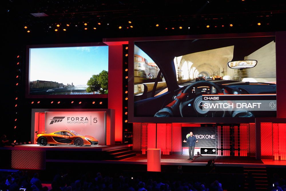 . Dan Greenawalt, developer of the video game Forza Motorsport, standing next to a McLaren sports car speak after unveiling Forza Motorsport 5 video game for Xbox during Microsoft Xbox news conference with a at the Electronic Entertainment Expo at the Galen Center on June 10, 2013 in Los Angeles, California. Thousands are expected to attend the annual three-day convention to see the latest games and announcements from the gaming industry.  (Photo by Kevork Djansezian/Getty Images)