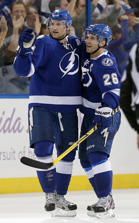 . Tampa Bay Lightning center Steven Stamkos (91) celebrates with right wing Martin St. Louis (26) after scoring against the Minnesota Wild during the third period. (AP Photo/Chris O\'Meara)