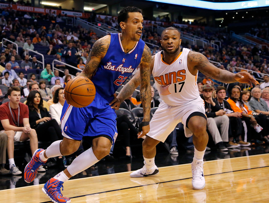 . Los Angeles Clippers forward Matt Barnes (22) drives past Phoenix Suns forward P.J. Tucker (17) during the first half of an NBA basketball game on Wednesday, April 2, 2014, in Phoenix. (AP Photo/Matt York)
