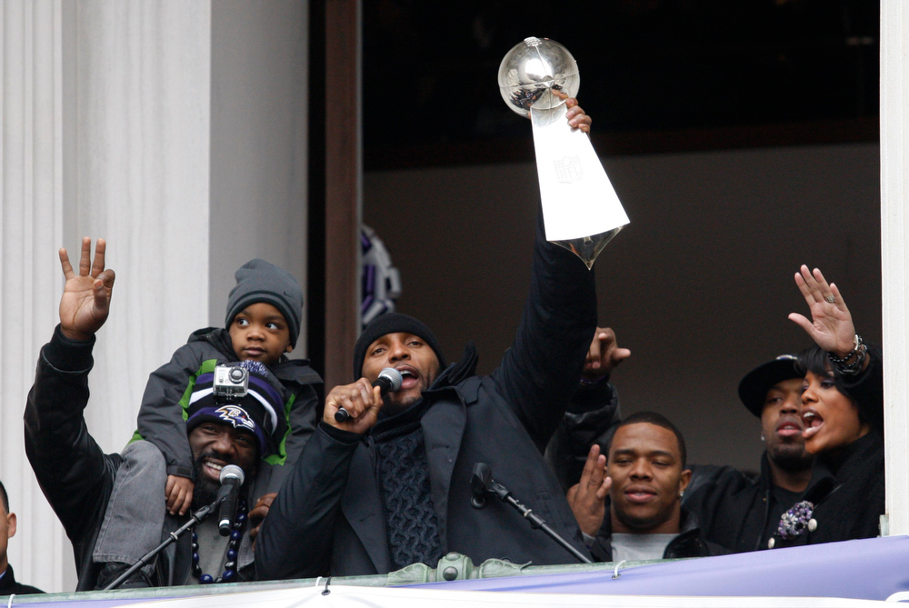 Description of . Baltimore Ravens retiring linebacker Ray Lewis (C) holds up the Vince Lombardi trophy as he stands with safety Ed Reed (L) during a rally at City Hall in Baltimore, Maryland February 5, 2013. The Ravens defeated the San Francisco 49ers to win the NFL championship.  REUTERS/Richard Clement