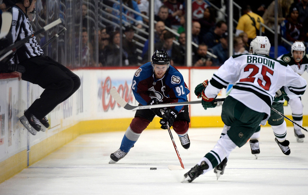 . DENVER, CO - APRIL 26: Colorado Avalanche left wing Gabriel Landeskog (92) takes the puck up ice against Minnesota Wild defenseman Jonas Brodin (25) during the first period of action. The Colorado Avalanche hosted the Minnesota Wild in the fifth round of the Stanley Cup Playoffs at the Pepsi Center in Denver, Colorado on Saturday, April 26, 2014. (Photo by John Leyba/The Denver Post)