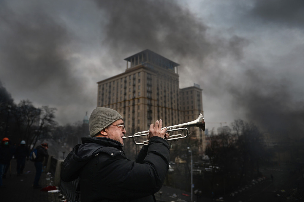 . A man plays the trumpet as anti-government protesters continue to clash with police in Independence square, despite a truce agreed between the Ukrainian president and opposition leaders on February 20, 2014 in Kiev, Ukraine.   (Photo by Jeff J Mitchell/Getty Images)