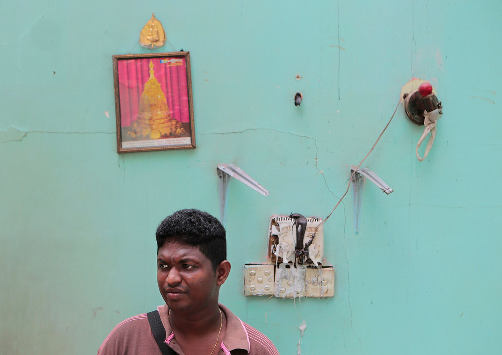 . In this Wednesday, June 25, 2014 photo, a Sri Lankan Buddhist youth stands inside a vandalized house in Darga Town, in Aluthgama about 50 kilometers (31 miles) south of Colombo, Sri Lanka. The onslaught by the Bodu Bala Sena (BBS), a hardline Buddhist group, killed two Muslims in the worst religious violence Sri Lanka has seen in decades. (AP Photo/Eranga Jayawardena)