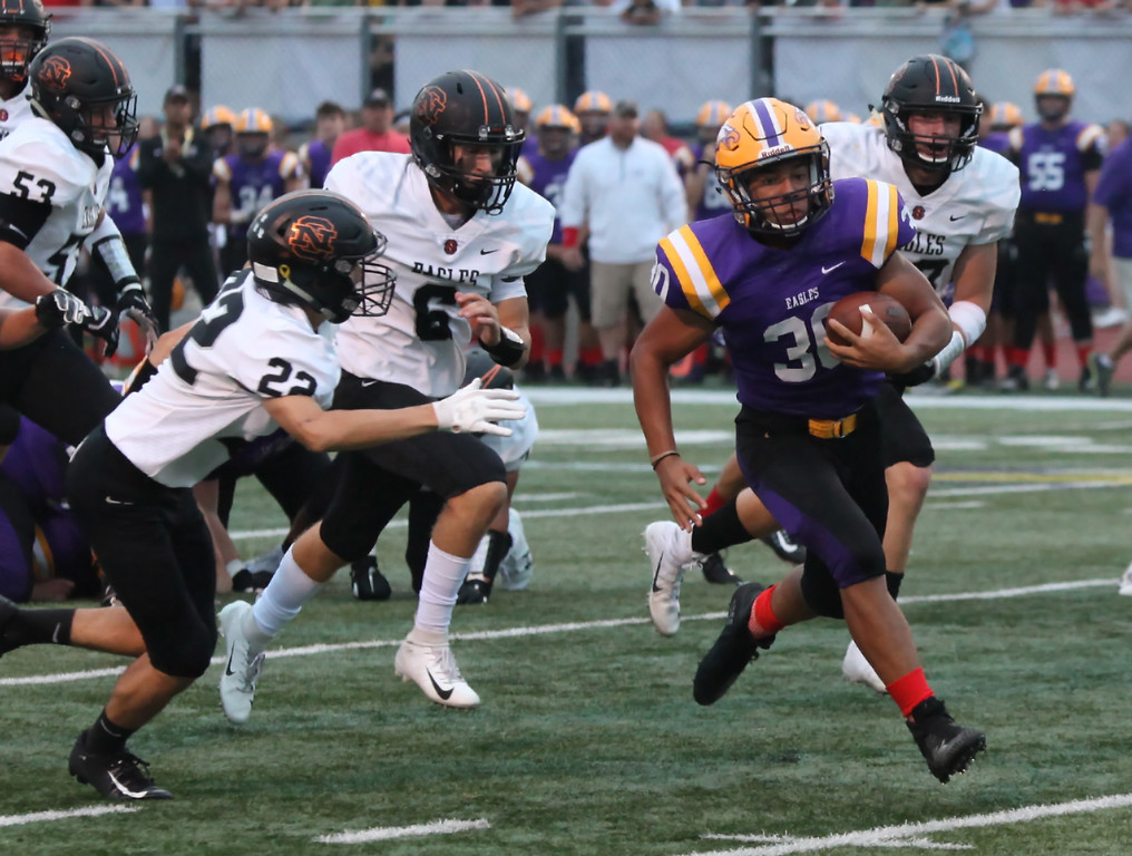 . Randy Meyers - The Morning Journal<br> Avon running back Devon Hunter breaks through the North Olmsted defense and will score the games first touchdown on Sept. 14.