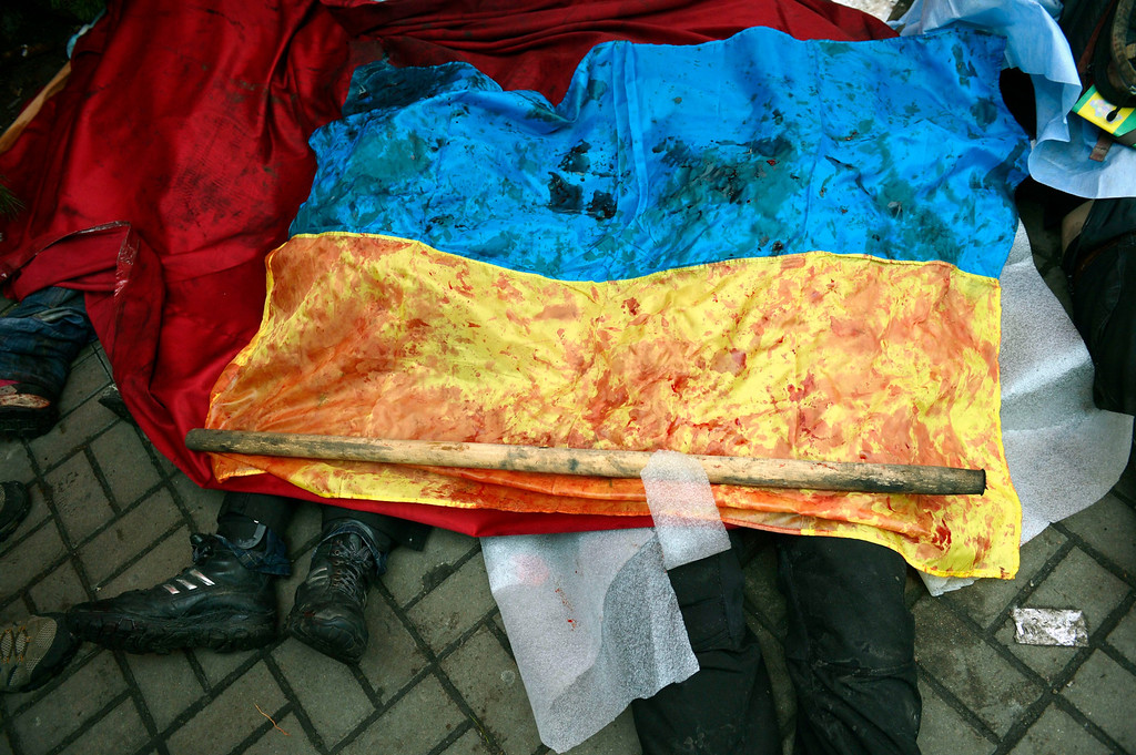. A bloody Ukranian flag covers the bodies of killed protesters in Kiev, Ukraine, 20 February 2014. More than 60 people have been killed in street fighting in Kiev on Thursday, the nationalist Svoboda opposition party says.  EPA/LASZLO BELICZAY