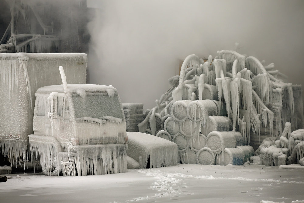 Description of . A truck is covered in ice as firefighters help to extinguish a massive blaze at a vacant warehouse on January 23, 2013 in Chicago, Illinois. More than 200 firefighters battled a five-alarm fire as temperatures were in the single digits. (Photo by Scott Olson/Getty Images)
