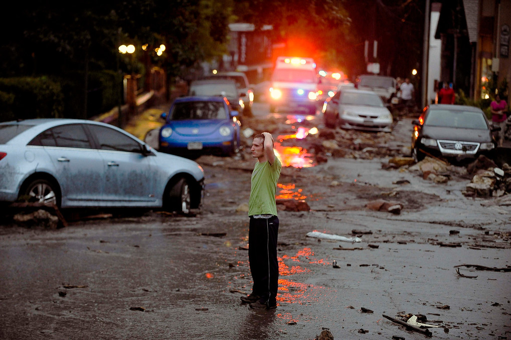 . Carson Dennis stands in the middle of the destruction caused by a flash flood that poured down Canon Avenue, Friday, Aug. 9, 2013 in Manitou, Colo. A mudslide has closed U.S. 24 between Cascade and Manitou Springs, and flash flooding in Manitou Springs is stranding vehicles in high, fast-moving water. (AP Photo/The Colorado Springs Gazette, Michael Ciaglo)