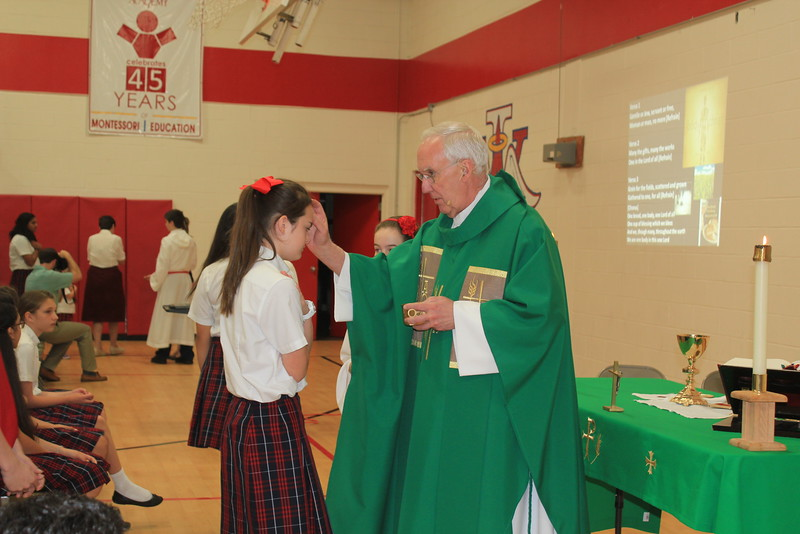 Monsignor Roger Smith blesses IWA seventh grader Cameron Martinez during a school Mass in honor of Mary.