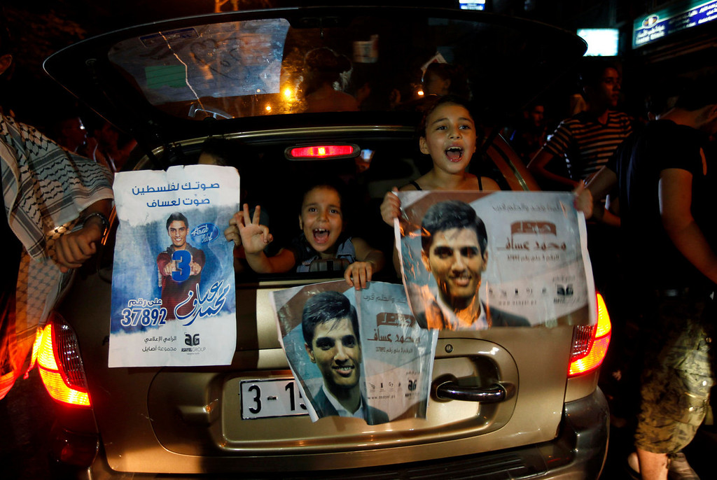 ". Palestinians celebrate after Palestinian singer Mohammed Assaf won a regional TV singing contest, along the streets of Gaza City, Saturday, June 22, 2013. Palestinians relished a rare moment of pride and national unity Saturday after the 23-year-old wedding singer from a refugee camp in the Gaza Strip won ""Arab Idol,\"" a regional TV singing contest watched by millions of people.  (AP Photo/Hatem Moussa)"