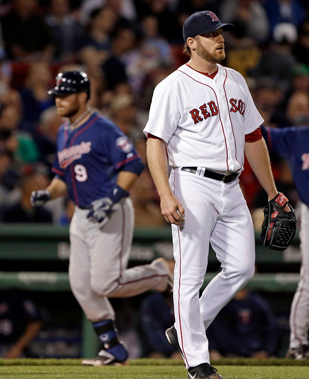 . Boston Red Sox starting pitcher Ryan Dempster reacts as Minnesota Twins designated hitter Ryan Doumit (9) rounds third after hitting a solo home run during the seventh inning of a baseball game at Fenway Park in Boston, Tuesday, May 7, 2013. (AP Photo/Elise Amendola)