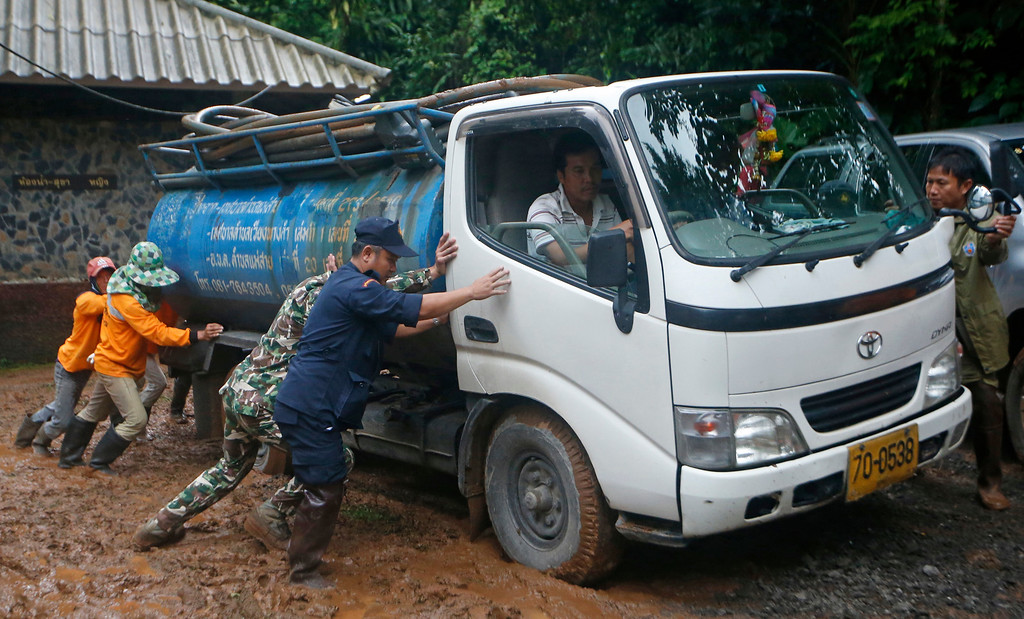 . In this Thursday, June 28, 2018, photo, soldiers and volunteers push a fresh water truck stuck in mud in the staging area for the missing soccer team and their coach who are believed to be missing in a large cave in Mae Sai, Chiang Rai province, in northern Thailand. (AP Photo/Sakchai Lalit)