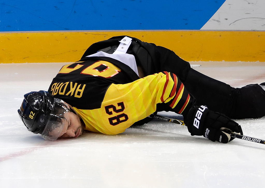 . Sinan Akdag (82), of Germany, falls on ice after getting checked by Tommy Kristiansen (15), of Norway, during the second period of the preliminary round of the men\'s hockey game at the 2018 Winter Olympics in Gangneung, South Korea, Sunday, Feb. 18, 2018. (AP Photo/Matt Slocum)