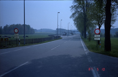 This location is the border of West Germany and the East German Deutsche Demokratische Republic --the Communist DDR.  The gates and guard shack is that of the last stop in West Germany, and the actual boarder is about a quarter mile up the road.  In the near distance on the left is one of the many closely spaced East German guard towers with orders to shoot to kill if any intruders from either side.  However, it is inconceivable any intruder would make it that far as the entire area is saturated with land mines, automatic machine guns, plus vicious police dogs trained to maul and kill.  Not a very friendly place!!   Note the notices on the signs on near right side.  That round red circle means STOP!! immediately ahead.
